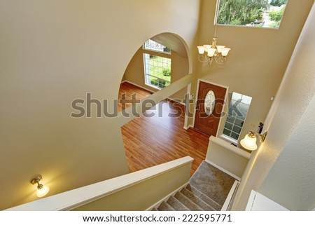 Panoramic view of entrance hallway with hardwood floor and archway. View  from staircase - stock photo