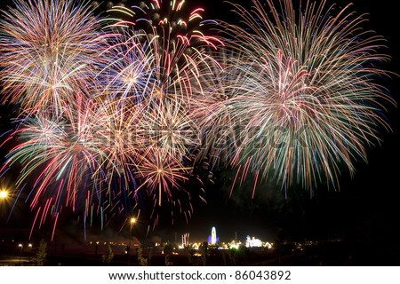 Panoramic view of fireworks over a fair in the night - stock photo