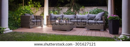 Panoramic view of garden patio with furniture - stock photo