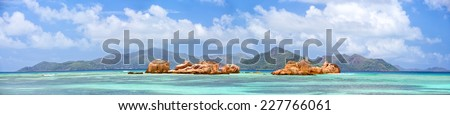 Panoramic view of granite rocks near La Digue coast with Praslin Island in background, Seychelles - stock photo