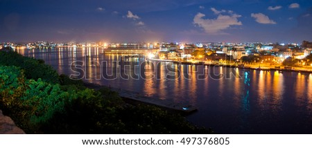 Panoramic view of Havana bay and skyline at night with light reflections on the water
