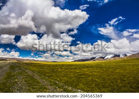 Panoramic view of high mountains. Meadow with green grass under blue sky with light clouds - stock photo