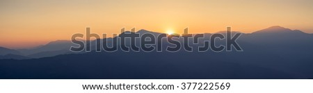 Panoramic view of hills and mountains with blue haze at golden hour and beautiful sunset - stock photo