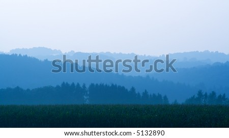 panoramic view of hills in different soft shades of blue behind a corn field