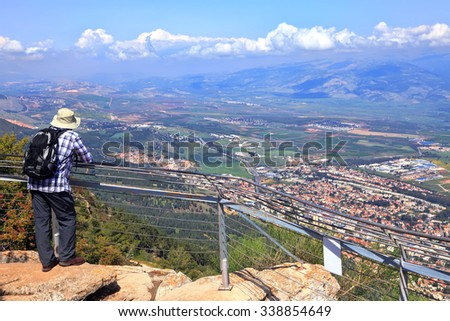 Panoramic view of Hula valley and traveler looking from top of Manara Cliff at Kiryat Shmona. North of Israel is the most popular travel site with locals and tourists in Israel - stock photo