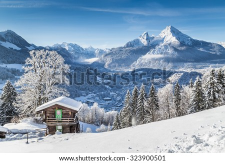 Panoramic view of idyllic winter wonderland mountain scenery with traditional mountain chalet in the Alps on a sunny day with blue sky - stock photo
