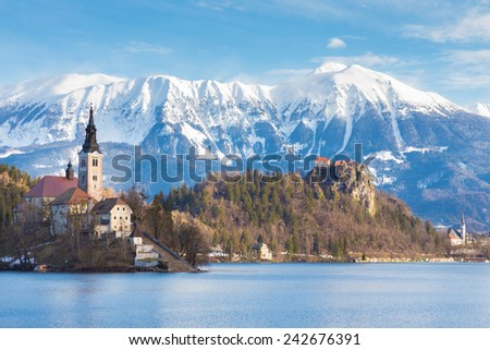 Panoramic view of Julian Alps, Lake Bled with St. Marys Church of the Assumption on the small island; Bled, Slovenia, Europe.  - stock photo