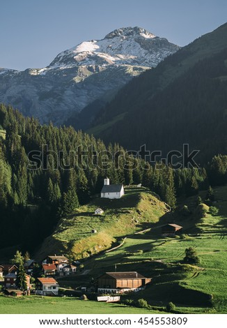 Panoramic view of little town Breil/Brigels, Switzerland with Sogn Sieve church in the middle - stock photo