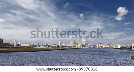 Panoramic view of London city from the London City Airport, showing Canary Wharf at the Isle of Dogs over River Thames. - stock photo