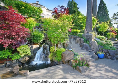 Panoramic View of Luxury Home Backyard, Professionally Landscaped with Waterfalls and Lush Vegetation - stock photo