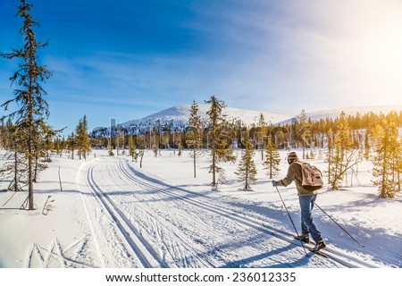 Panoramic view of male person cross-country skiing in beautiful nordic winter landscape in Scandinavia with blue sky and golden evening light at sunset, Europe - stock photo