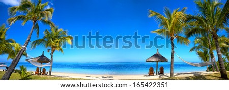 Panoramic view of Mauritius beach with chairs and umbrellas - stock photo