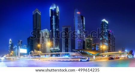 Panoramic view of metro station and road in Financial district at night, Dubai, UAE.