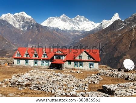 Panoramic view of Mount Everest, Lhotse and Ama Dablam from Kongde with tourist lodge - Sagarmatha national park - Nepal - stock photo