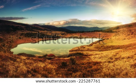 Panoramic view of mountain lake  with sunlight in Carpathian park. Autumn landscape.
