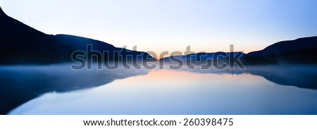 Panoramic view of mountain ridge silhouettes reflected in a still water of Polygonal lake in Kunijok valley, Hibiny mountains above the Arctic circle, Russia - stock photo