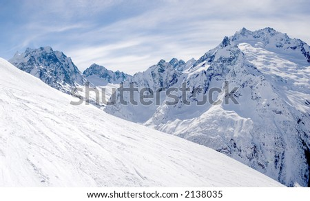 panoramic view of mountain slope with the tracks of skis and boards - stock photo