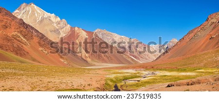 Panoramic view of mountain valley in the Andes with hikers trekking, Argentina, South America - stock photo