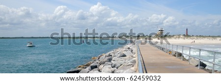 Panoramic view of New Smyrna beach with Ponce Lighthouse and lifeguard station in the background and the inlet from the rock jetty walkway. - stock photo