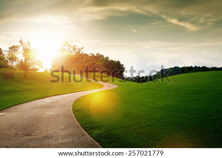 panoramic view of nice green hill and path during sunset - stock photo
