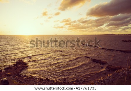 Panoramic view of ocean beach shore with rocks and sunset view landscape. - stock photo