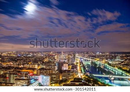 Panoramic view of Paris city from Eiffel tower in moonlit night - stock photo