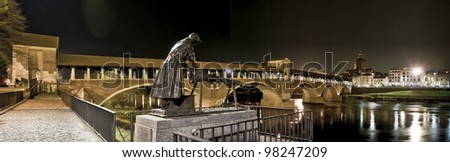 Panoramic view of Pavia, Italy, by night: the laundress statue, the covered Bridge over Ticino river and the Dome - stock photo