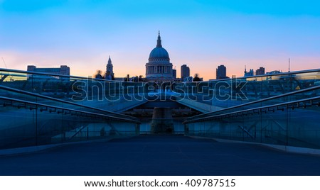 Panoramic view of pink sunset at St Paul's Cathedral and the Millennium Bridge in London with people walking in blurred motion