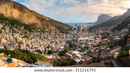 Panoramic view of Rio's Rocinha favela, on a sunny afternoon.  Visible in the distance is the South Atlantic Ocean. The high-rise buildings near the coast are condominiums in Sao Conrado - stock photo