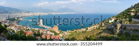 Panoramic view of sea port of Alanya. In the foreground the ruins of an ancient fortress. In the background of the Taurus mountains and residential neighborhoods of Alanya. Turkey. - stock photo