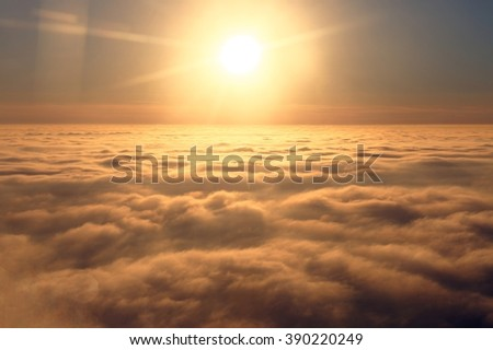 Panoramic view of sky above clouds from the window of plane - stock photo