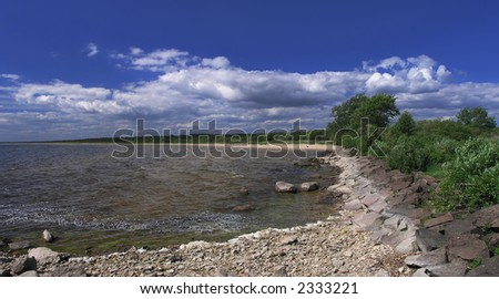 Panoramic view of stony lakeshore - stock photo