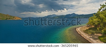 panoramic view of storm approaching islands in Hisaronu bay in Aegean sea with sun shining through clouds, Turkey - stock photo