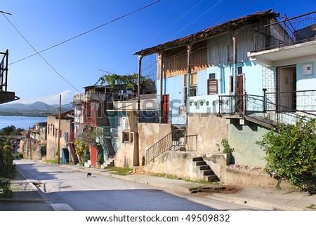 Panoramic view of street with crumbling buildings and view on a bay in Santiago de Cuba , Cuba - stock photo
