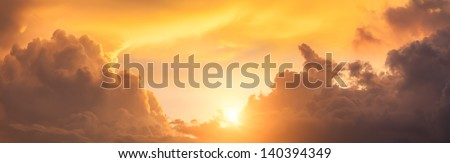 panoramic view of sunset sky with dramatic clouds and sun - stock photo