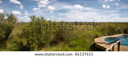 Panoramic view of swimming pool in the bush in the Delta of Okavango, Botswana. - stock photo