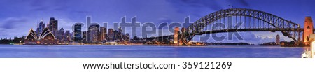 panoramic view of Sydney cityscape at sunset across Harbour from Kirribilli. CBD landmarks and Harbour bridge are under illumination - stock photo