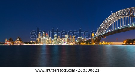 Panoramic view of Sydney over the harbour with Harbour Bridge in foreground and CBD in background. Twilight view with city lights and lights from ferries on the harbour.