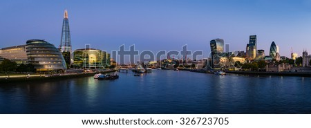 Panoramic view of Thames river with modern London cityscape reflecting the colors of sunrise