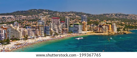 Panoramic view of the beach town. On the beach a lot of sunbathers and swimmers people among the multicolored umbrellas (View Benidorm, Spain)
