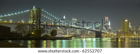 Panoramic view of the Brooklyn Bridge and New York skyline at night from Brooklyn. - stock photo
