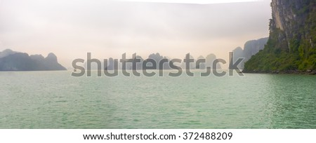 Panoramic view of the dramatic and mysterious Halong Bay, Vietnam. The Bay is dotted with strange limestone islands This is a popular tourist destination. - stock photo