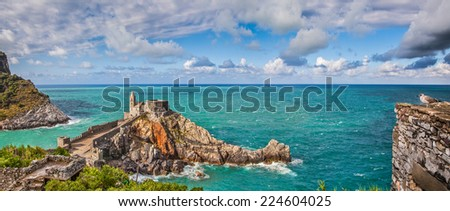 Panoramic view of the famous gothic Church of St. Peter (Chiesa di San Pietro) with seagull on a rock in the town of Porto Venere, Ligurian Coast, province of La Spezia, Italy - stock photo