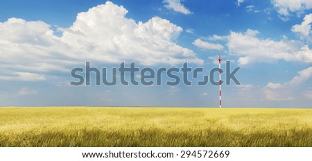 panoramic view of the field with rye . TV tower in the field. communication in rural areas. Background photo . focus on the tower and sky