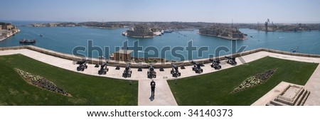 Panoramic view of the Grand Harbour, Valletta, from the Upper Barrakka Gardens with Saluting Battery in Foreground and an reenactment actor giving a speech before a demonstration of a battery Salute. - stock photo