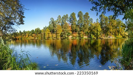 Panoramic view of the lake with autumn yellow and green trees, natural seasonal background - stock photo