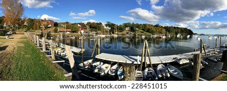 panoramic view of the Rockport Marine harbor in Maine.  There are many boats moored by the dock as well as many boats anchored in the water.   - stock photo