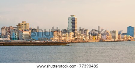 Panoramic view of the seashore of Havana with the famous promenade of El Malecon illuminated by the light of the sunset - stock photo