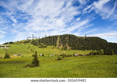 panoramic view of the Seiser Alm in a sunny day with blue sky and clouds