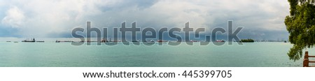 Panoramic view of the Singapore Strait from Sentosa Island. Ships, industrial landscape and stormy weather. - stock photo